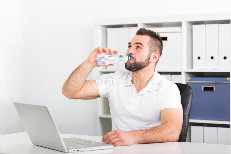 Stiligt drinkvatten för ung man från en flaska arkivfoton