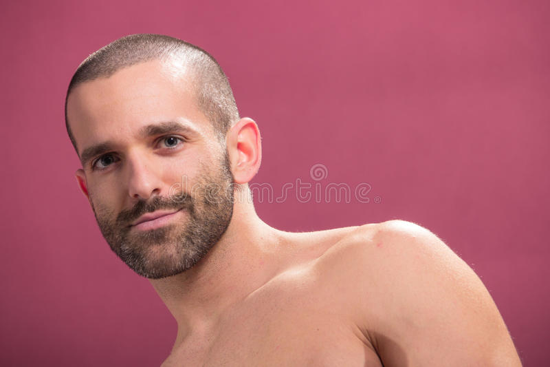 Stiligt för rosa bakgrund för ung man smila shirtless arkivfoto