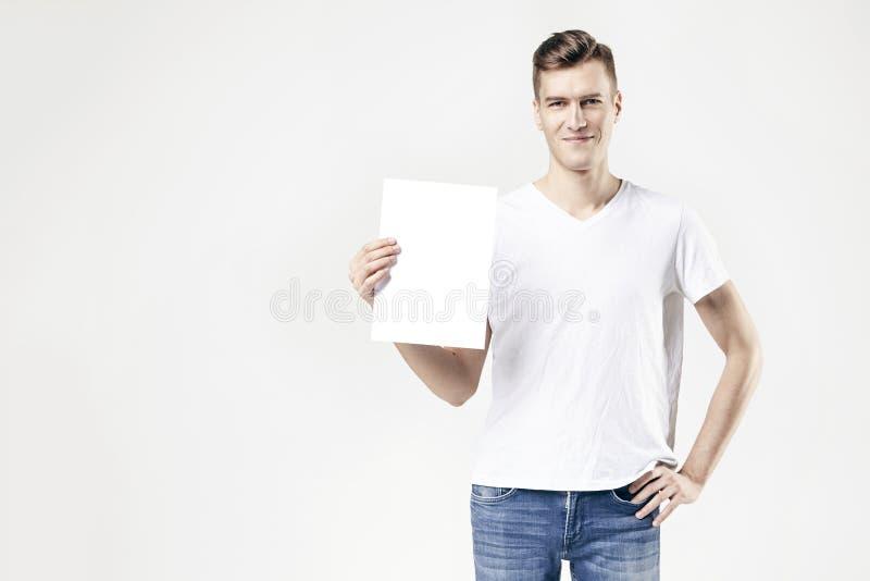 Stiligt grabbanseende med det tomma arket i handen som isoleras på vit bakgrund, bärande jeans och t-skjortan tillgängligt utrymm arkivfoto