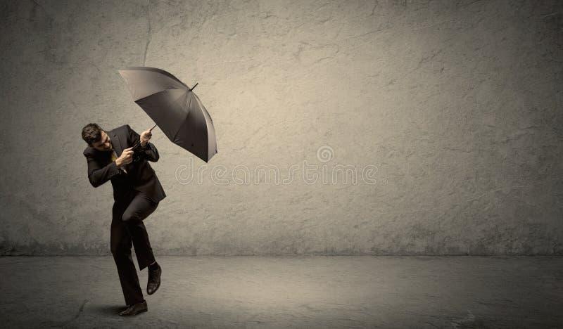Stiligt hållande paraply för affärsman med kopieringsutrymmebakgrund fotografering för bildbyråer