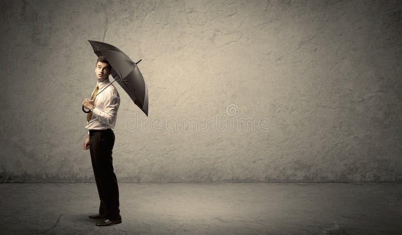 Stiligt hållande paraply för affärsman med kopieringsutrymmebakgrund arkivfoton