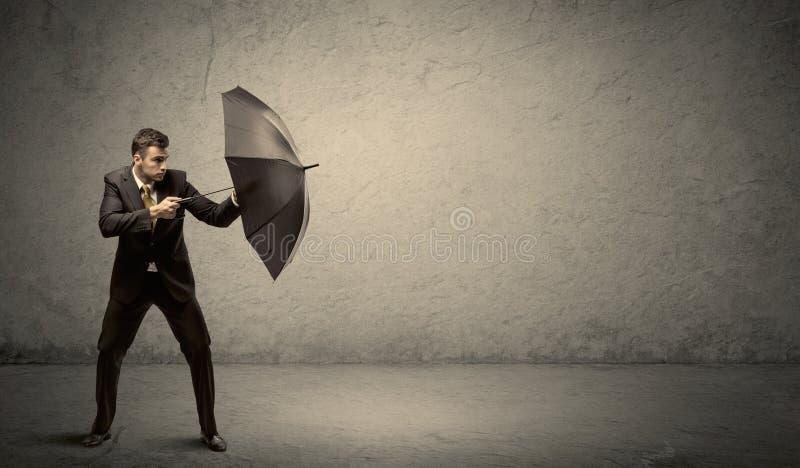 Stiligt hållande paraply för affärsman med kopieringsutrymmebakgrund royaltyfria foton