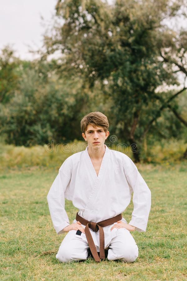 Stiligt karatestudentsammanträde på en naturlig bakgrund Östligt stridighetkursbegrepp kopiera avstånd arkivfoto