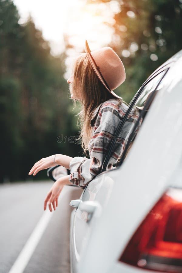 Stiligt kvinnasammanträde i bilen som ser från fönster på härlig sikt i den nätta flickahipsteren för skog som tycker om landsväg royaltyfri bild