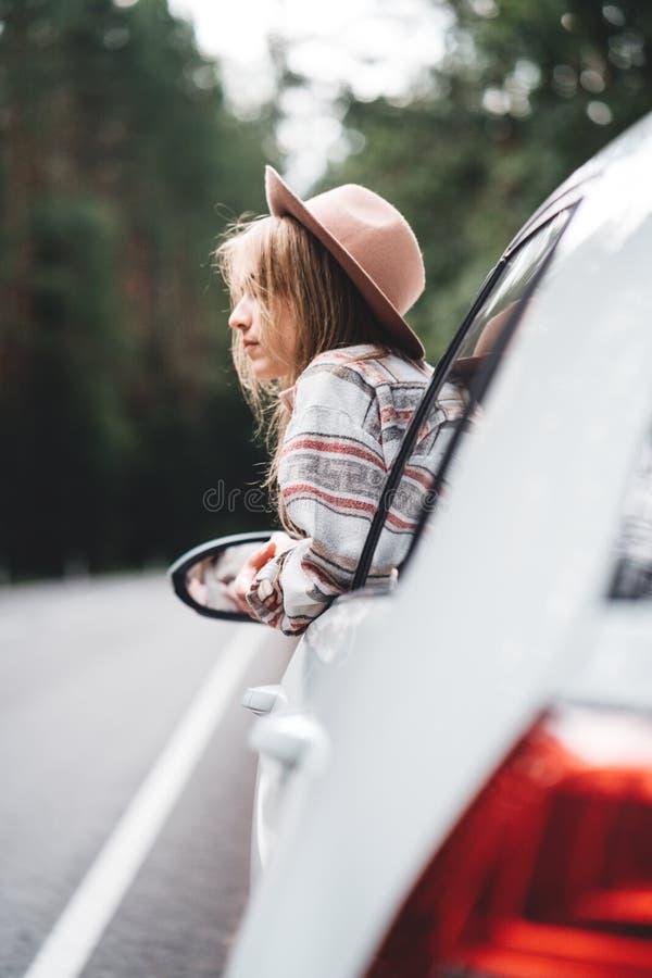 Stiligt kvinnasammanträde i bilen som ser från fönster på härlig sikt i den nätta flickahipsteren för skog som tycker om landsväg royaltyfria foton