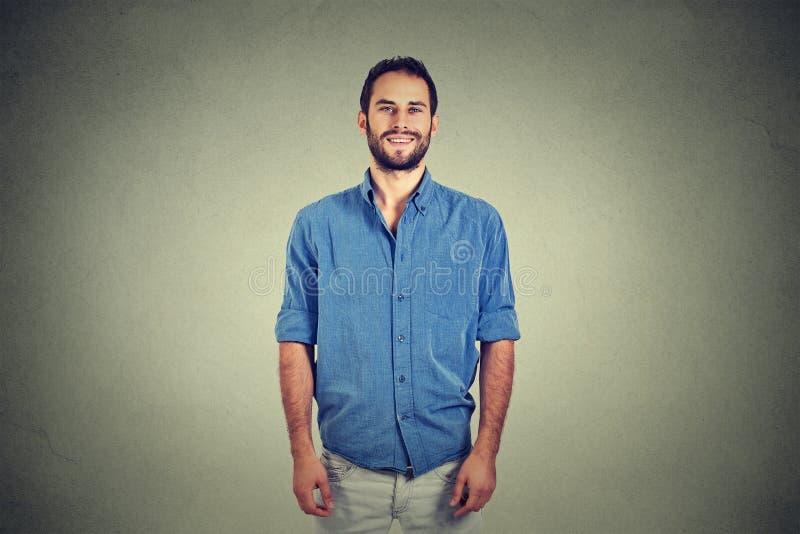 Stiligt le för ung man som isoleras mot grå väggbakgrund arkivbild