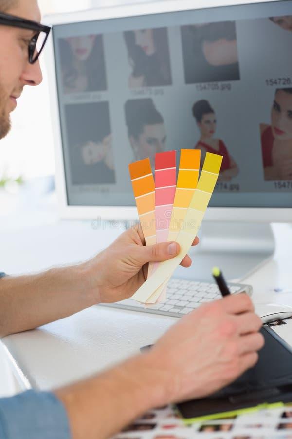 Stiligt märkes- arbete med det hållande färgdiagrammet för digitizer på hans skrivbord arkivfoto