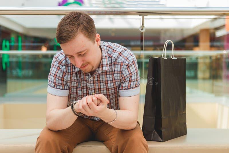 Stiligt mansammanträde i lager och se hans klocka fotografering för bildbyråer