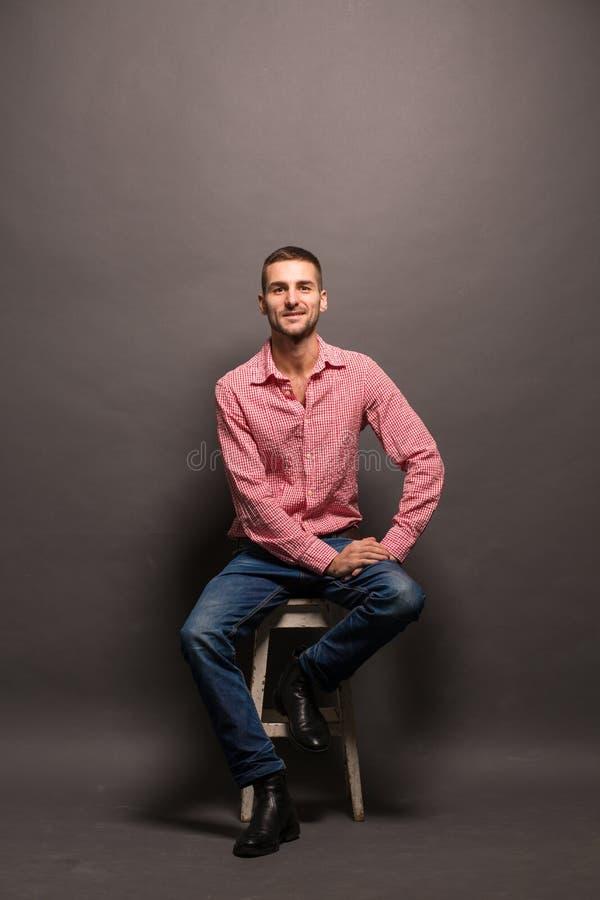 Stiligt mansammanträde på en stol i studio royaltyfri fotografi