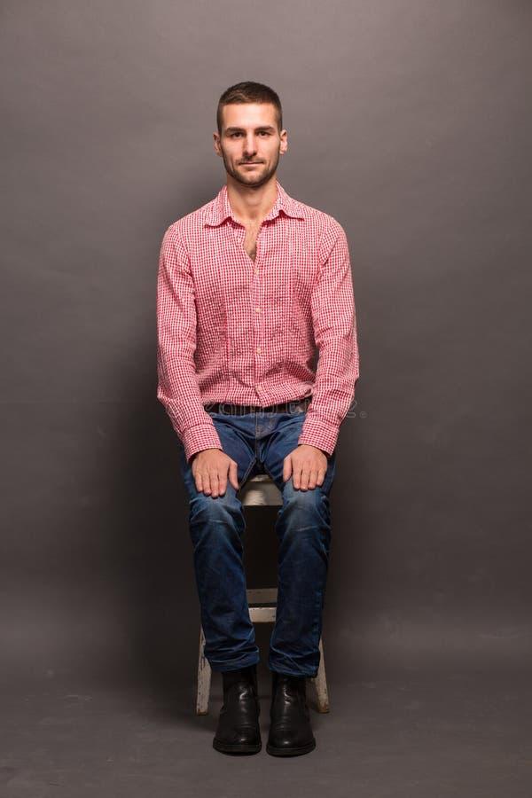 Stiligt mansammanträde på en stol i studio fotografering för bildbyråer