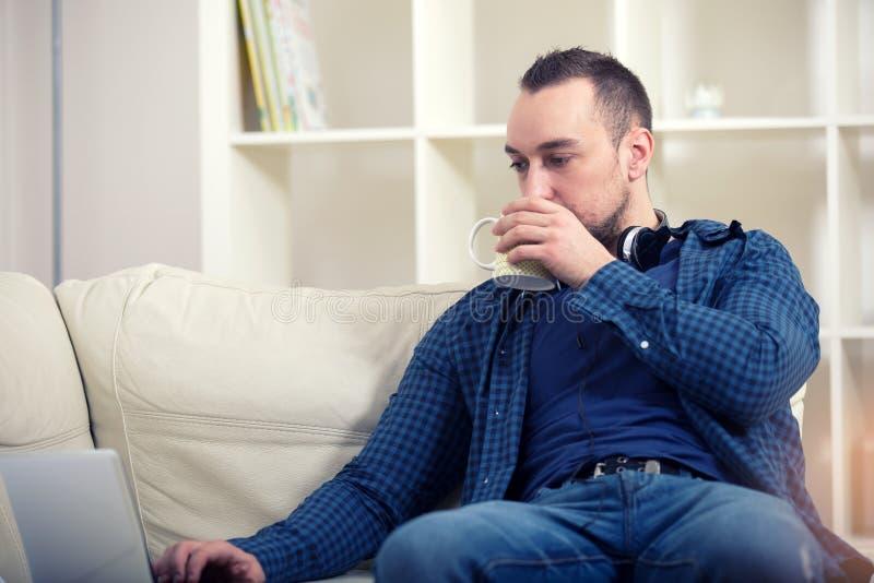 Stiligt mansammanträde på soffan med bärbara datorn royaltyfria foton