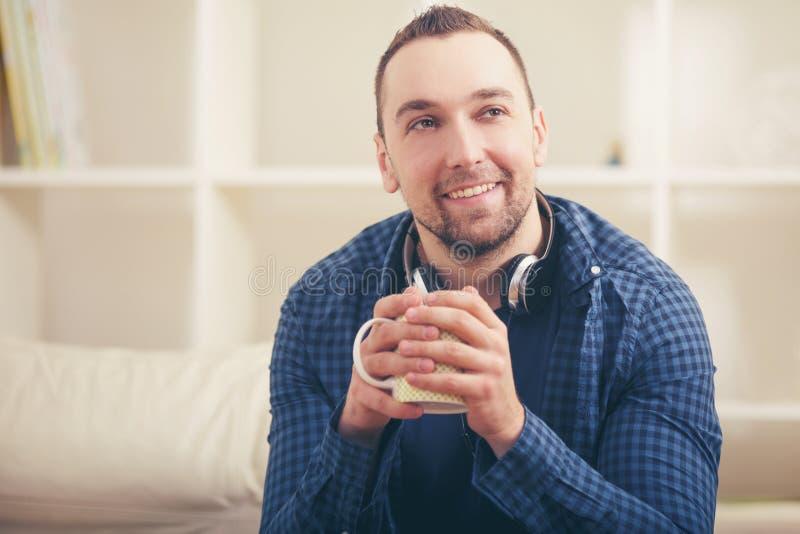 Stiligt mansammanträde på soffan med kopp te arkivbilder