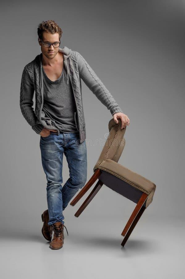 Stiligt med stol. Stiliga unga män i exponeringsglas som lutar på th royaltyfri fotografi