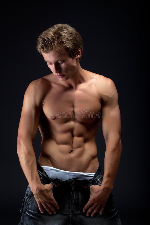Stiligt muskulöst blont posera för man tar av jeans royaltyfri bild