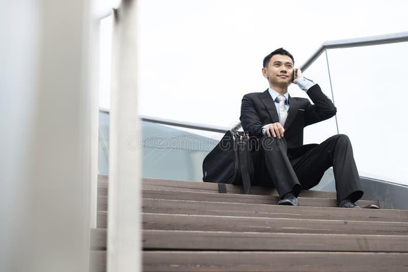 Stiligt sammanträde för mobiltelefon för affärsman talande i trappan fotografering för bildbyråer