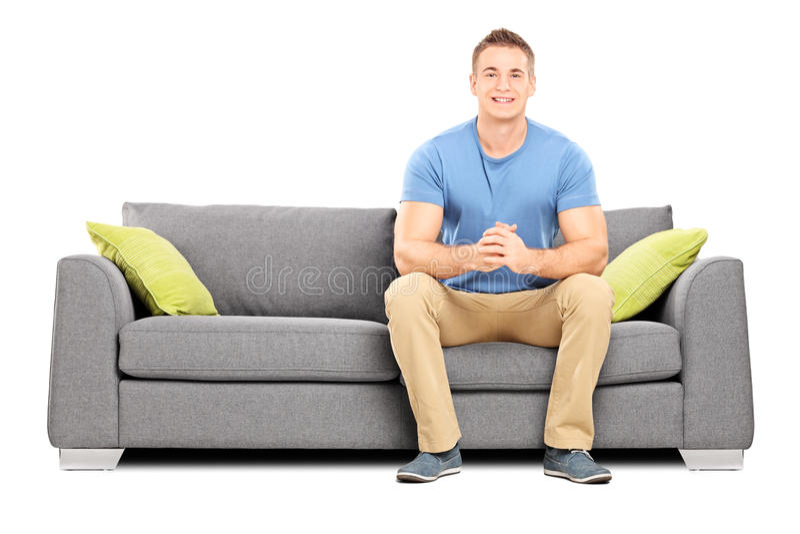 Stiligt sammanträde för ung man på en modern soffa royaltyfri bild