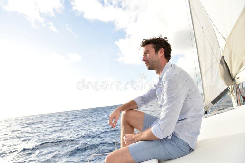 Stiligt sammanträde för ung man på segelbåten royaltyfri foto