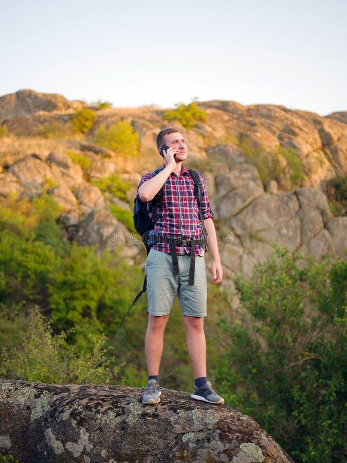 Stiligt turist- samtal på en telefon Ung man som kallar på en naturlig bakgrund Rikssamtalbegrepp kopiera avstånd royaltyfri foto