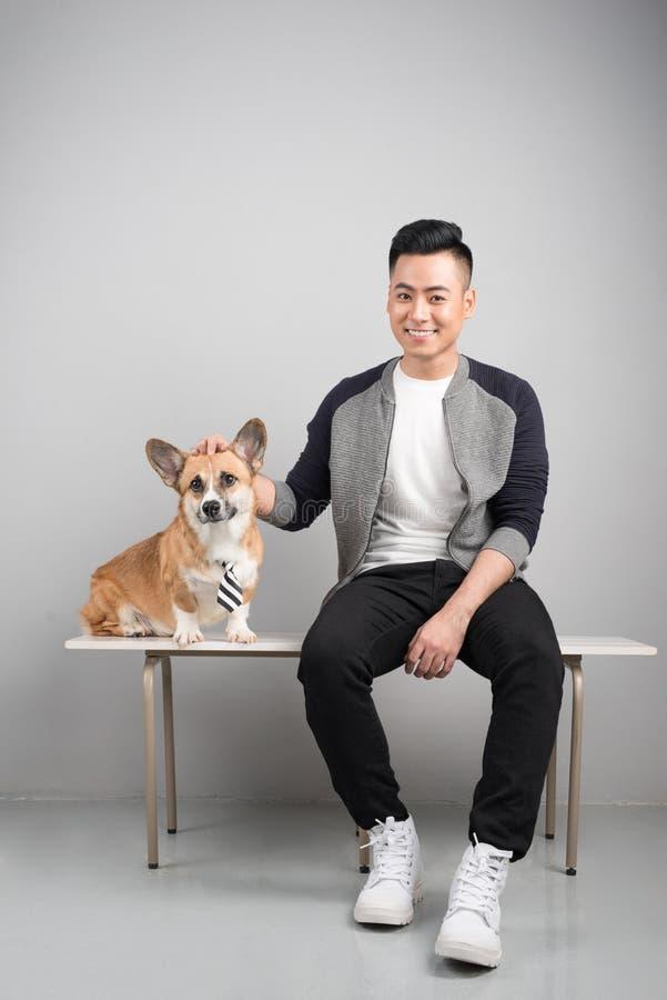 Stiligt ungt asiatiskt mansammanträde med hans hund på stol fotografering för bildbyråer