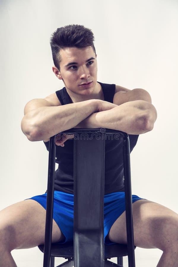 Stiligt ungt muskulöst mansammanträde på stol arkivbild