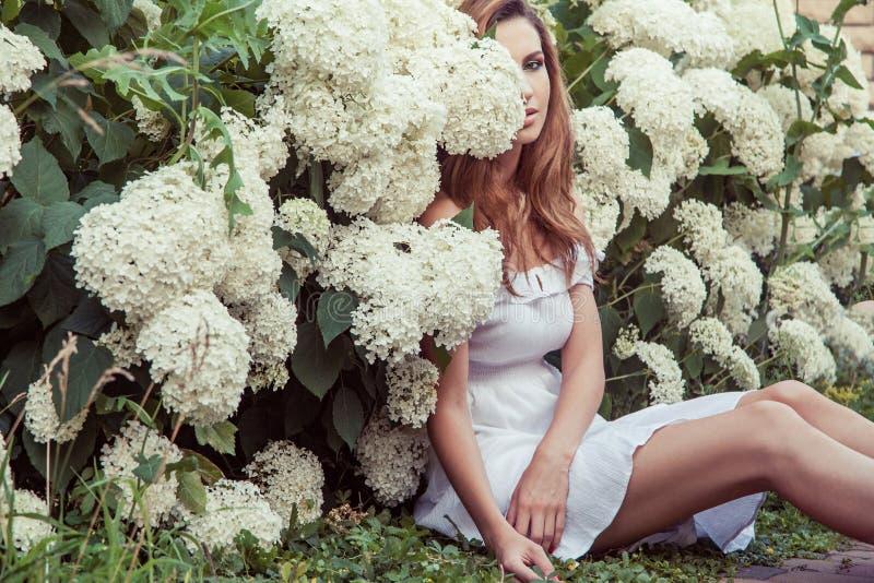 Stiligt ungt sammanträde för den vuxna kvinnan nära många blommar parkerar in royaltyfri bild