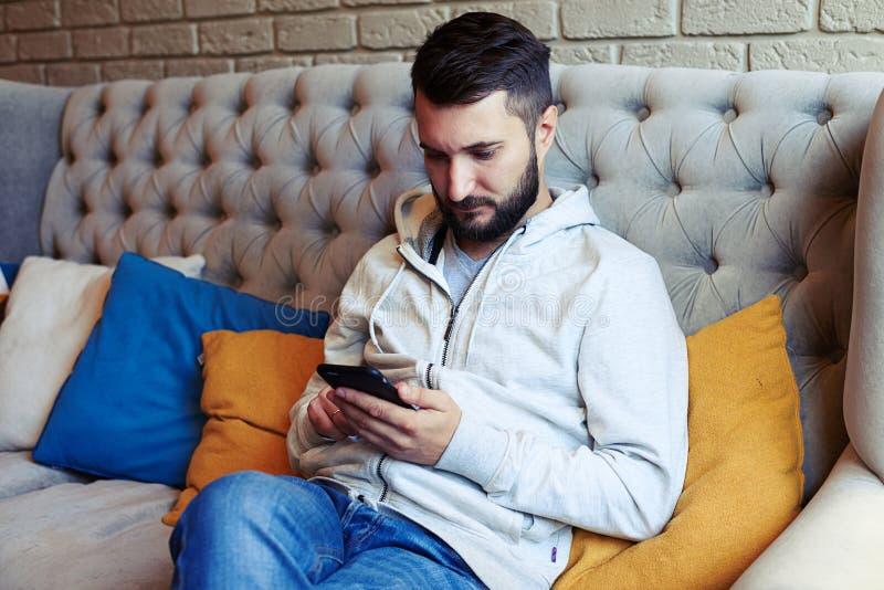 Stiligt ungt vuxet mansammanträde på soffan arkivfoto