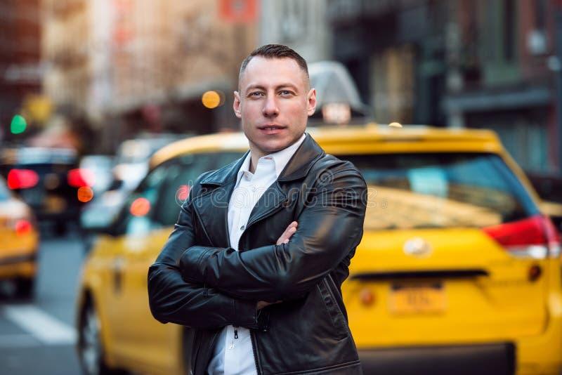 Stiligt vuxet mananseende på stadsgatan med armar som korsas och ses kameran Livsstilfoto av mannen i New York City bil t royaltyfri bild