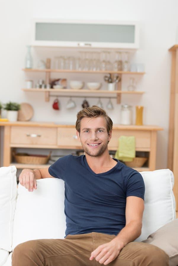 Stiligt younmansammanträde på en soffa royaltyfria foton