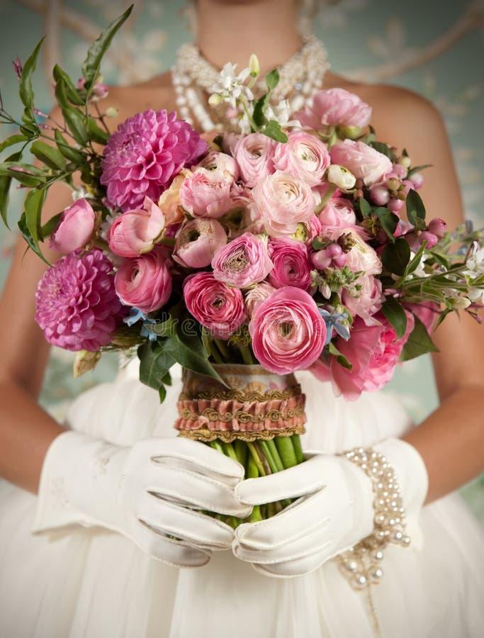 Stiliserad brud som rymmer den härliga buketten royaltyfri fotografi