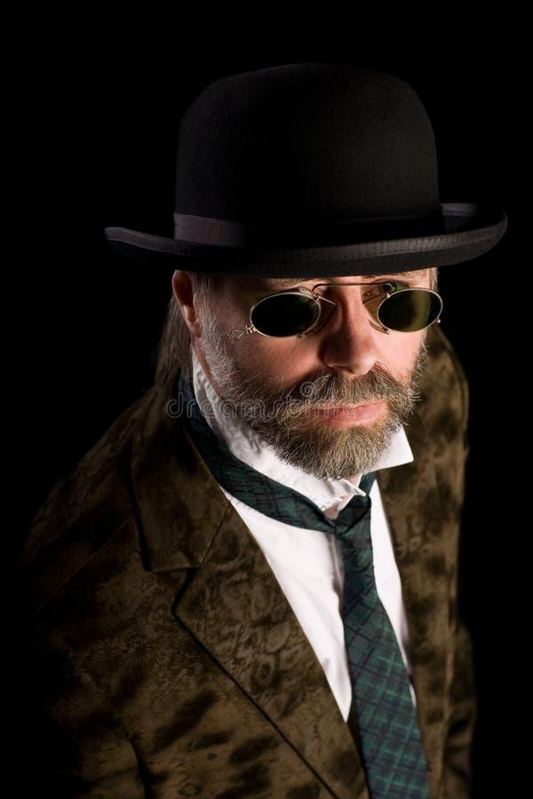 Stilish man in vintage pince nez. Stilish man in vintage sunglasses pince nez and bowler hat stock images