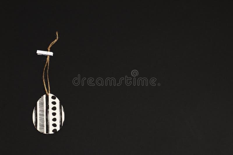 Stilisiertes dekoratives Ei in Schwarzweiss auf Jutefaserschnur mit Wäscheklammer auf schwarzem Hintergrund Minimalismusart stockfotografie