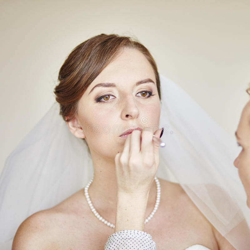 Stilist, der junge Braut vor der Heirat bildet stockbild