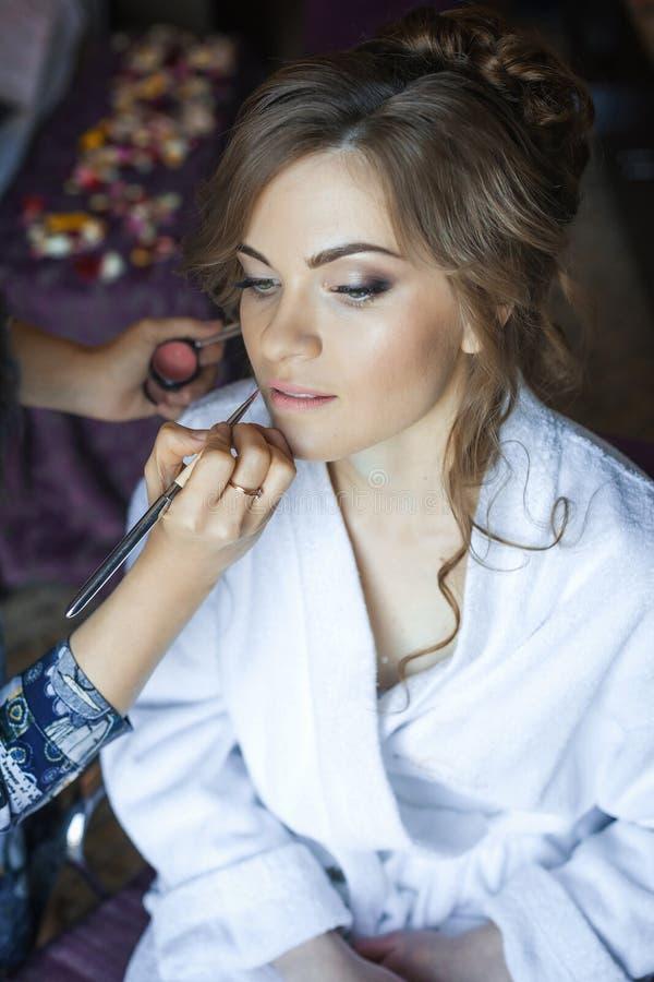 Stilist, der Make-upmädchen am Hochzeitstag macht lizenzfreie stockfotografie