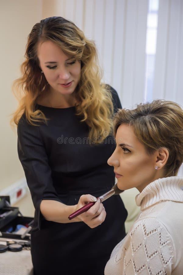 Stilist die make-upmodel doen royalty-vrije stock foto