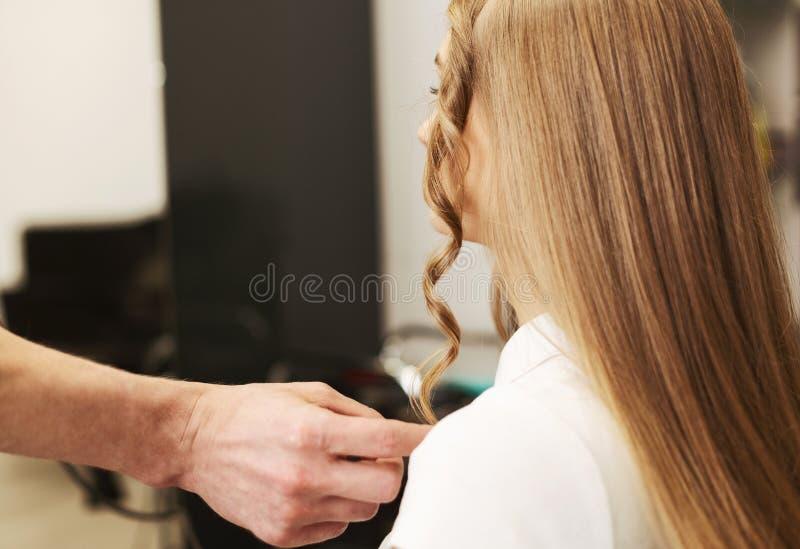 Stilist die tot Krullend Haar maken aan Cliënt in Schoonheidsstudio stock fotografie