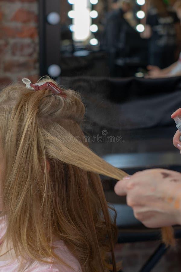 Stilist krullend haar voor jonge vrouw Meisjeszorg over haar kapsel Om krullen te doen stock foto