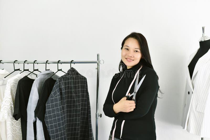 Stilista asiatico che lavora nel suo studio della sala d'esposizione, femminile nel negozio di vestiti del progettista fotografia stock libera da diritti