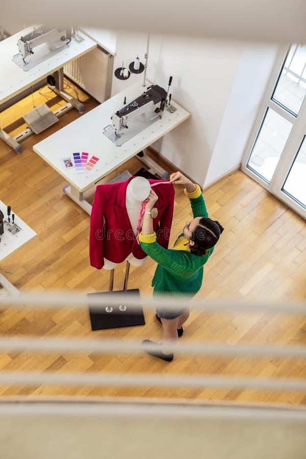 Stilista asiatico moro in un funzionamento della minigonna con un manichino immagine stock