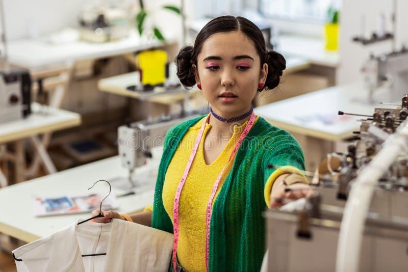Stilista asiatico sveglio con i braccialetti luminosi che sembrano occupati fotografia stock libera da diritti