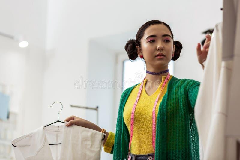 Stilista asiatico sveglio con i braccialetti luminosi che sembrano seri fotografie stock