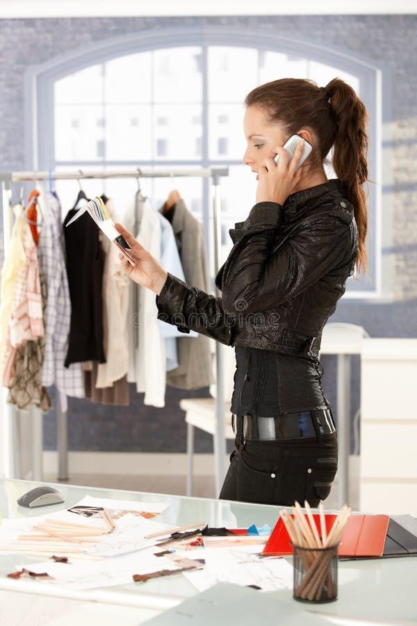 Stilista attraente che comunica sul telefono fotografia stock