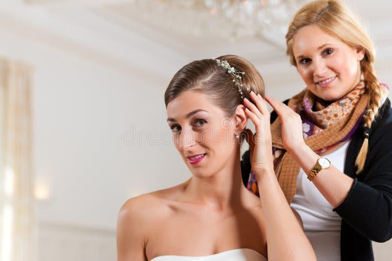 Stilista che appunta sull'acconciatura della sposa immagini stock