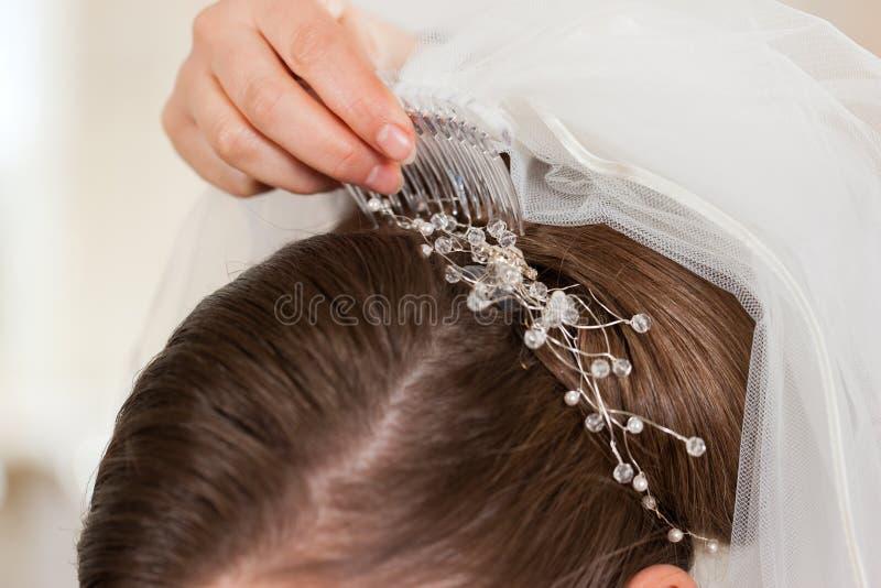 Stilista che appunta sull'acconciatura della sposa fotografie stock