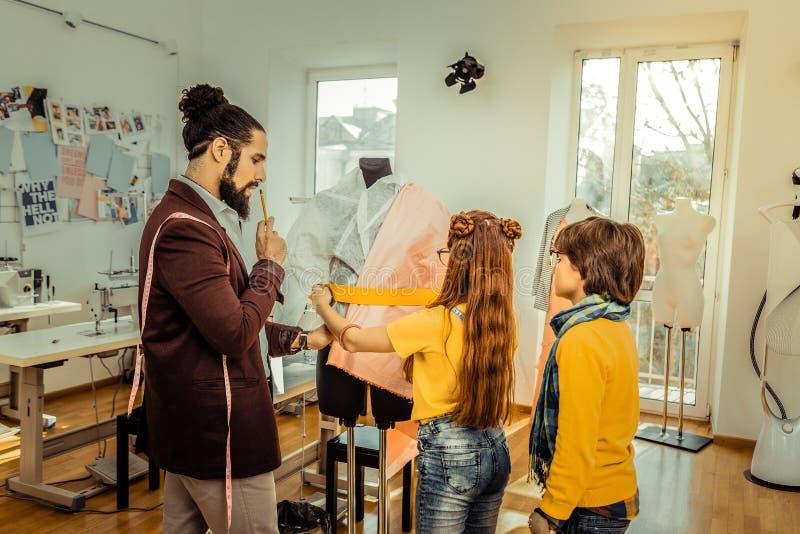 Stilista che insegna ai piccoli bambini che vanno adattare scuola immagine stock