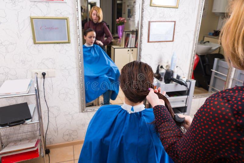 Stilista che pettina capelli bagnati della donna in salone fotografie stock libere da diritti