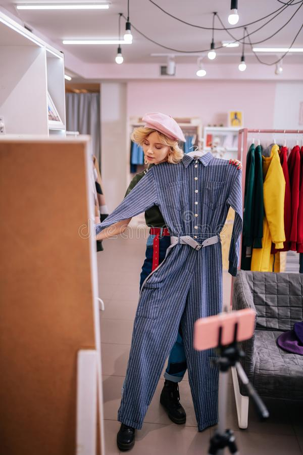 Stilista che porta berretto rosa che mostra il vestito alla moda del saltatore immagini stock