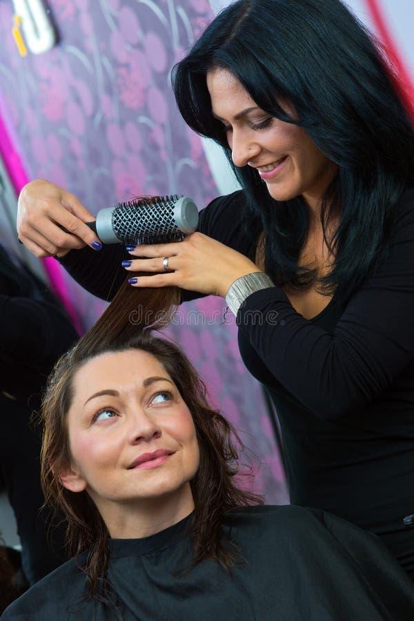 Stilista che rende a donna nuova acconciatura immagine stock