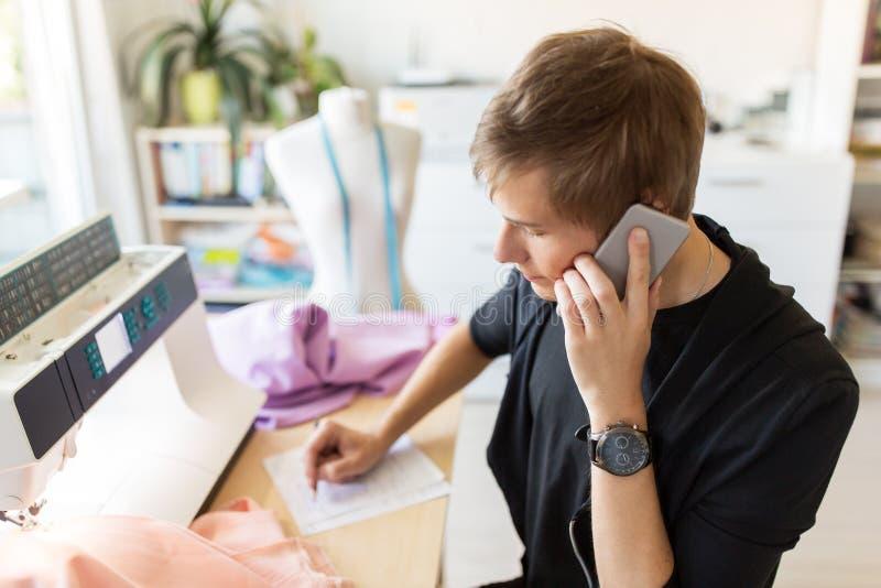 Stilista che rivolge allo smartphone allo studio immagine stock