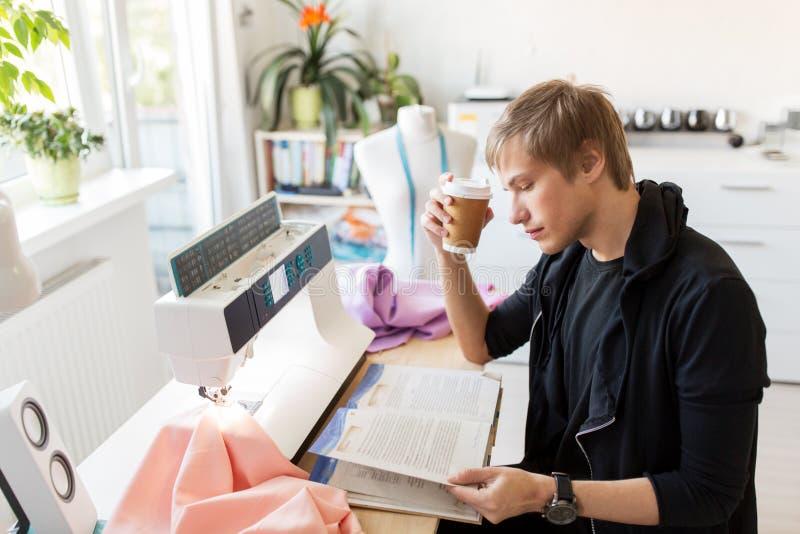 Stilista con caffè ed il libro allo studio immagini stock