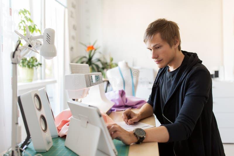 Stilista con il pc della compressa che funziona allo studio immagine stock libera da diritti